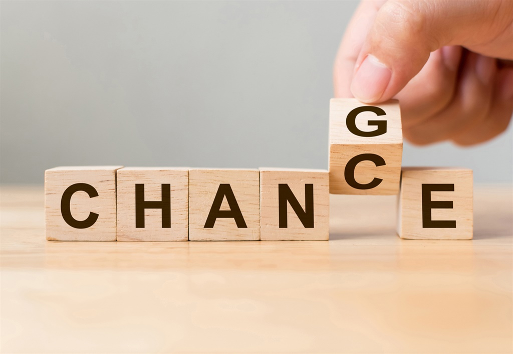Hand flip wooden cube with word change to chance,