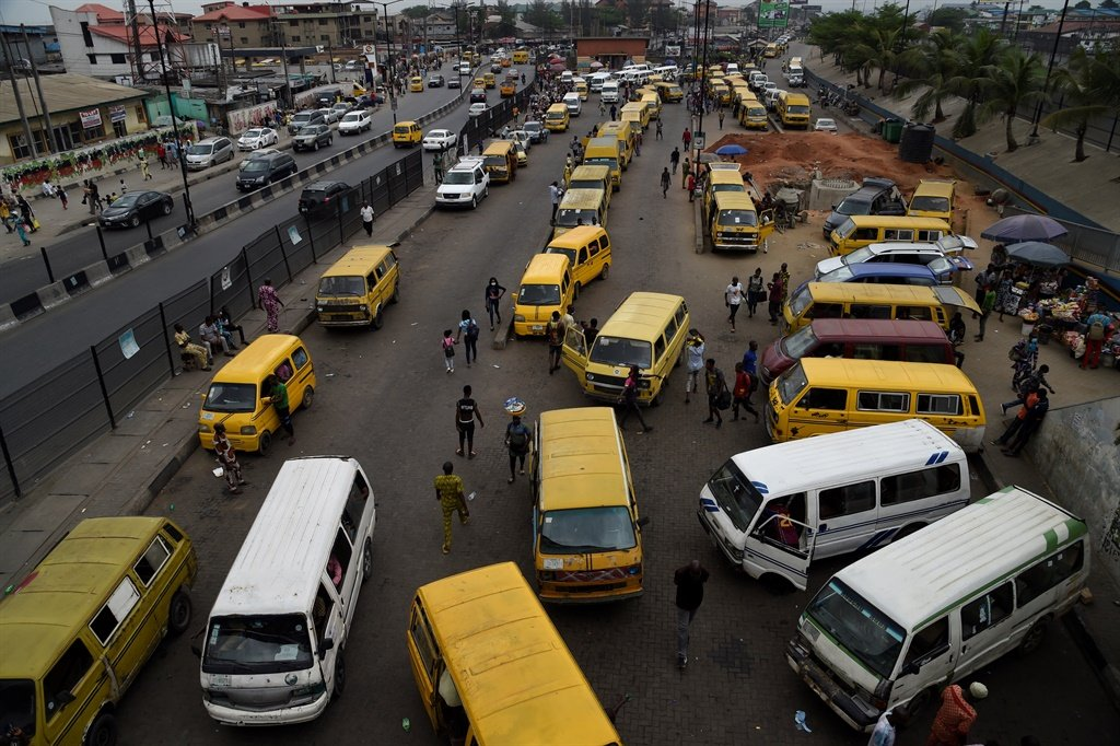 Economic activites slow down as a few passengers arrive to board buses parked longer hours at the Ojodu-Berger bus terminal in Nigeria. (AFP