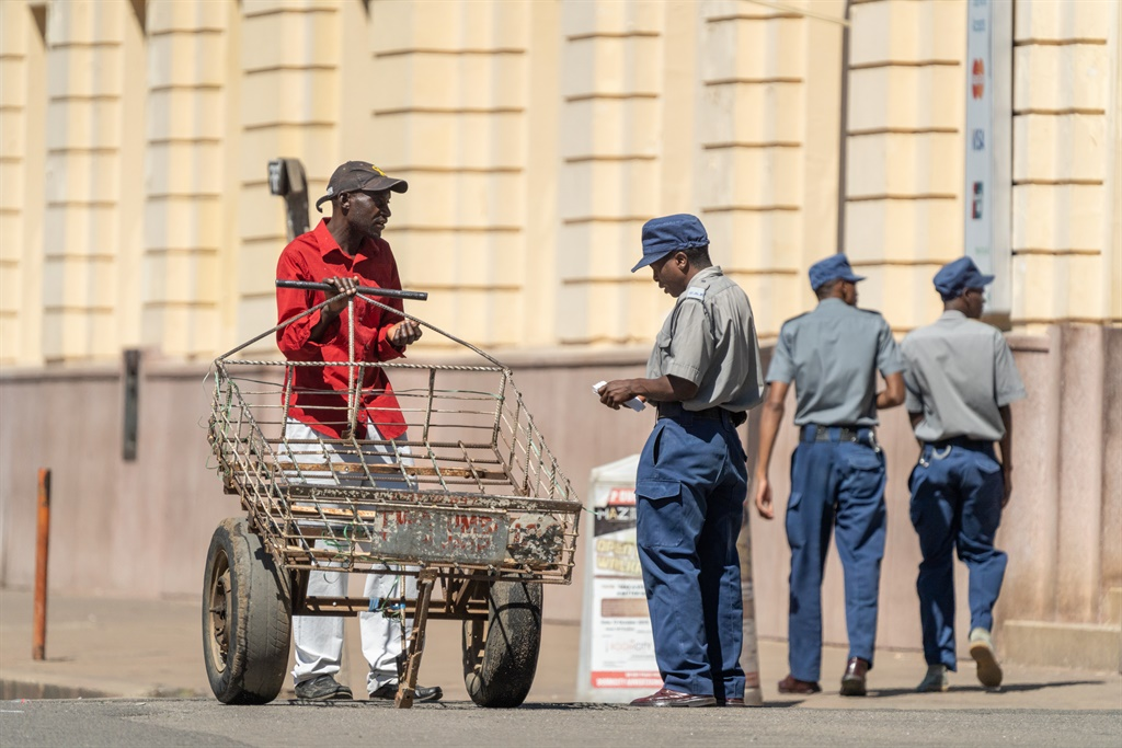 Police officers patrolling the streets order a man pushing a handcart to go home on the first day of a 21 day lockdown in Bulawayo, Zimbabwe. (AFP)