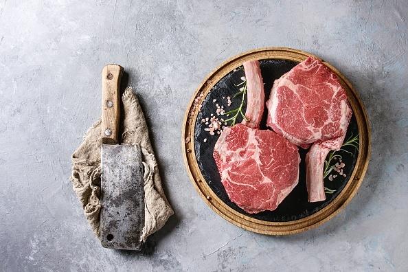 Raw uncooked black angus beef tomahawk steaks on b