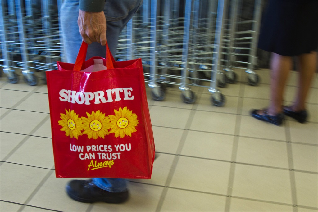 A customers carries a Shoprite-branded shopping ba