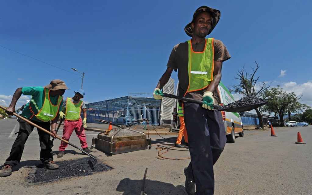 Pro-Phalt workers fix a pothole in Echo Road on Monday morning.