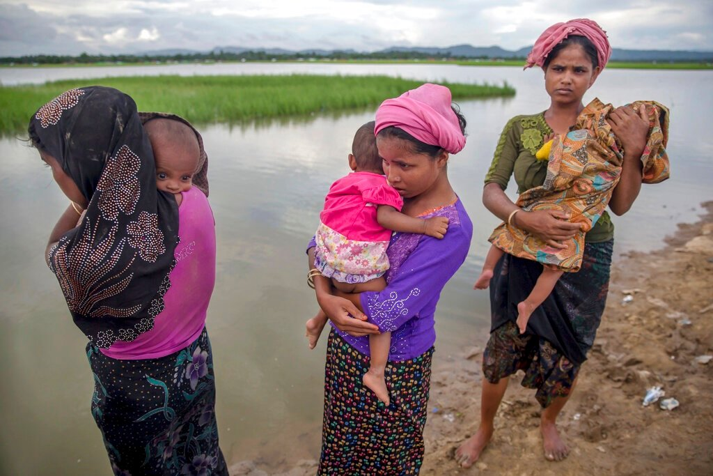 Rohingya Muslim women, who crossed over from Myanmar into Bangladesh, stand holding their sick children after Bangladesh border guard soldiers refused to let them journey towards a hospital. (Dar Yasin, AP, File)