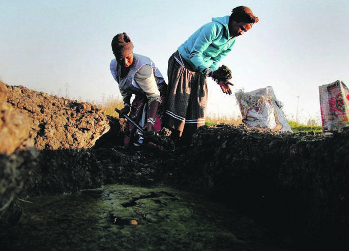 Two unemployed mothers dig for soft yellow clay in Soweto. They make their own coal from the clay Picture: Moeletsi Mabe / The Times / Gallo Images