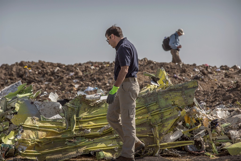 Foreign investigators examine wreckage at the scene where the Ethiopian Airlines Boeing 737 Max 8 crashed shortly after takeoff on Sunday killing all 157 on board. (Mulugeta Ayene, AP)