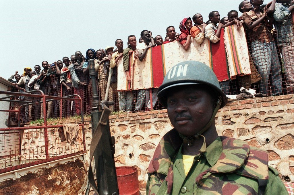 A Ghanaian United Nations soldier watches over some Tutsi refugees 20 June 1994 in Kigali, as they are evacuated from the Holy Family church to Kabuga on the outskirts of the Rwandan capital. (File, AFP)