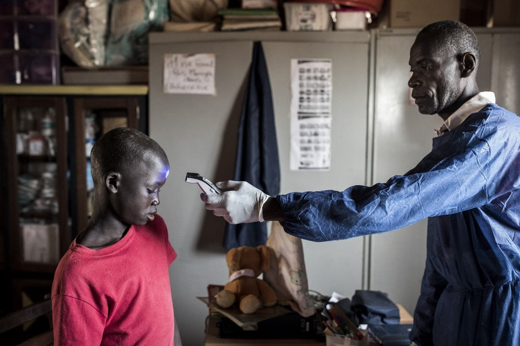 A child gets his temperature measured in a quarantined area outside Dakar.