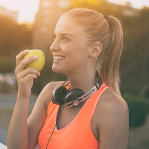 Sporty woman eating apple