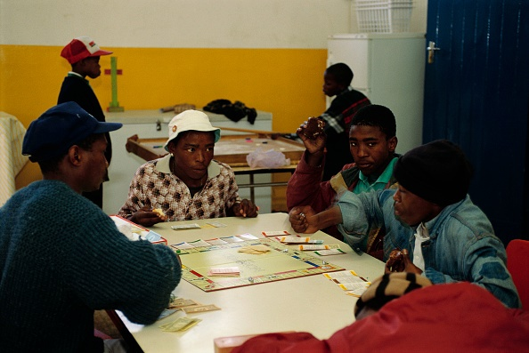Young Men Playing Monopoly (Photo by © Louise Gub