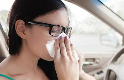 Woman blowing her nose in car