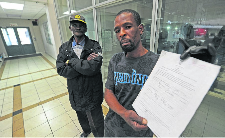 Bongumusa Dlamini holding up a copy of the interim protection order he obtained against Pietermaritzburg businessman, Yunus Goga. PHOTO: ian carbutt