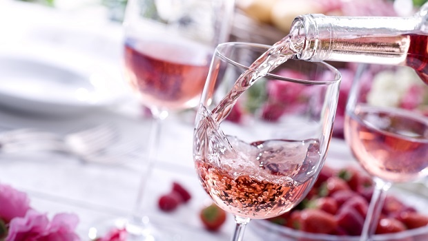 Close up of Rose wine being poured at a picnic setting.