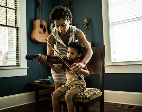 Mother helping young boy practice violin