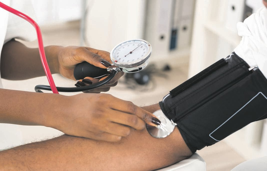 Close-up Of Doctor Measuring Patients Blood Pressure With Stethoscope.