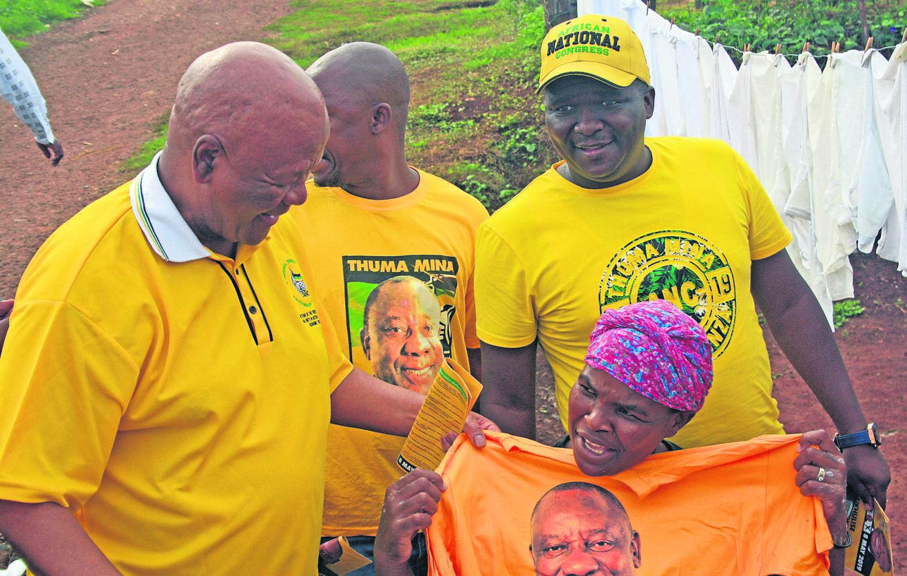 ANC senior leader Jeff Radebe, who was in an elections campaign trail in Tamboville on Monday, hands an ANC T-shirt to local resident Jabulile Mhlongo.
