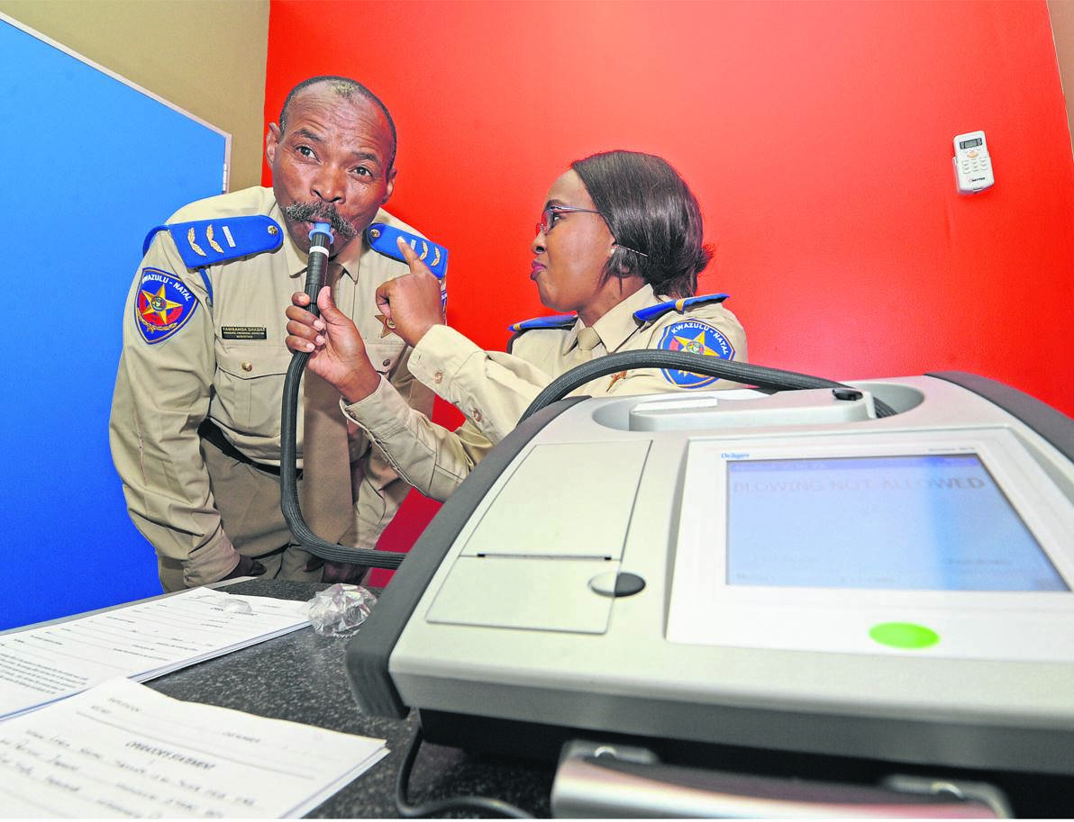 Provincial traffic inspectors Tamsanqa Shasha (left) and Nozipho Langa demonstrate how the Evidential Breathalyser Alcohol Testing (EBAT) machine works at the Alcohol Evidence Centre in Braid Street on Monday.