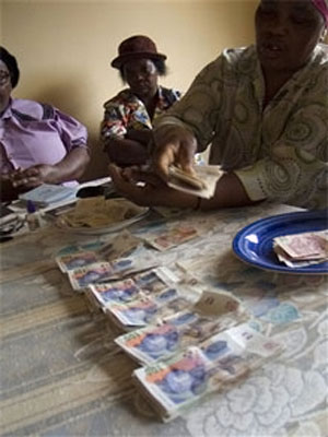 Women count money at a Stokvel meeting in Nhlazuka. (John Robinson, AP file)