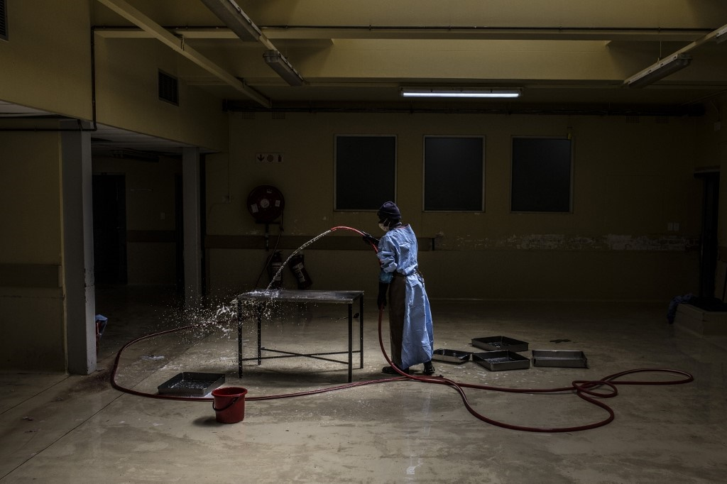 A worker washes a forensic tray after being used d