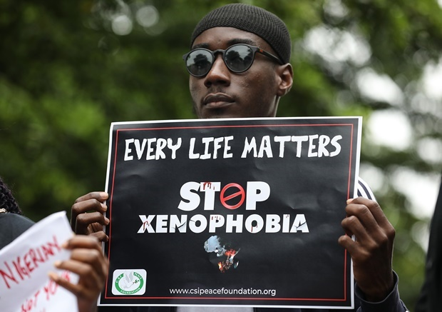 A demonstrator holds a sign during a protest against xenophobia outside of the main gate of the South African High Commission which was shut down to avert reprisal attacks in Abuja. (Kola Sulaimon, AFP)