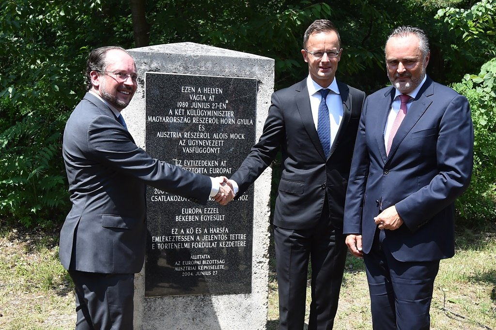 Austrian Burgenland's govenor Hans Peter Doskozil (R) looks on as Austrian Foreign Minister Alexander Schallenberg (L) shakes hand with his Hungarian counterpart Peter Szijjarto (C) in front of a memorial stone commemorationg the historical removal of fencing that represented the Iron Curtain. (Attila Kisbenedek, AFP)