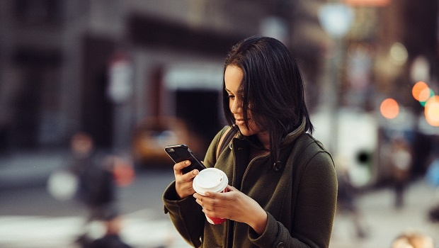 Young adult energetic woman texting on cell phone,