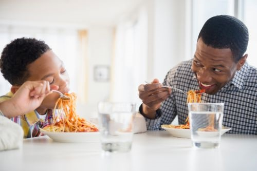 Father and son eating pasta