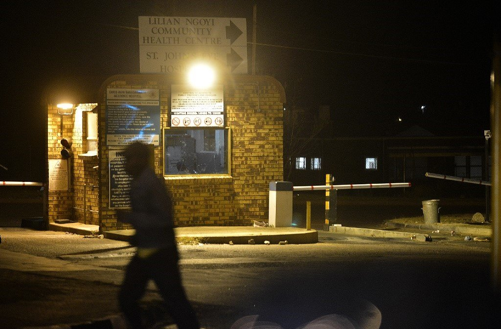A pedestrian walks by the community centre at the Chris Hani Baragwanath Hospital in Soweto. (AFP)