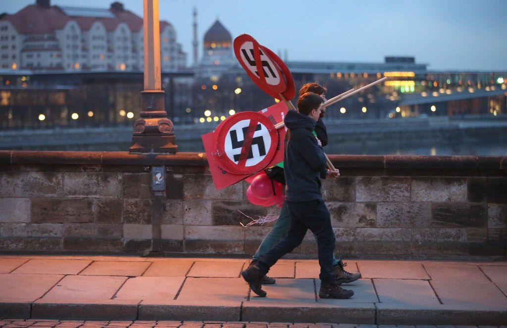 Anti-neo-Nazi activists carry signs showing swastikas.