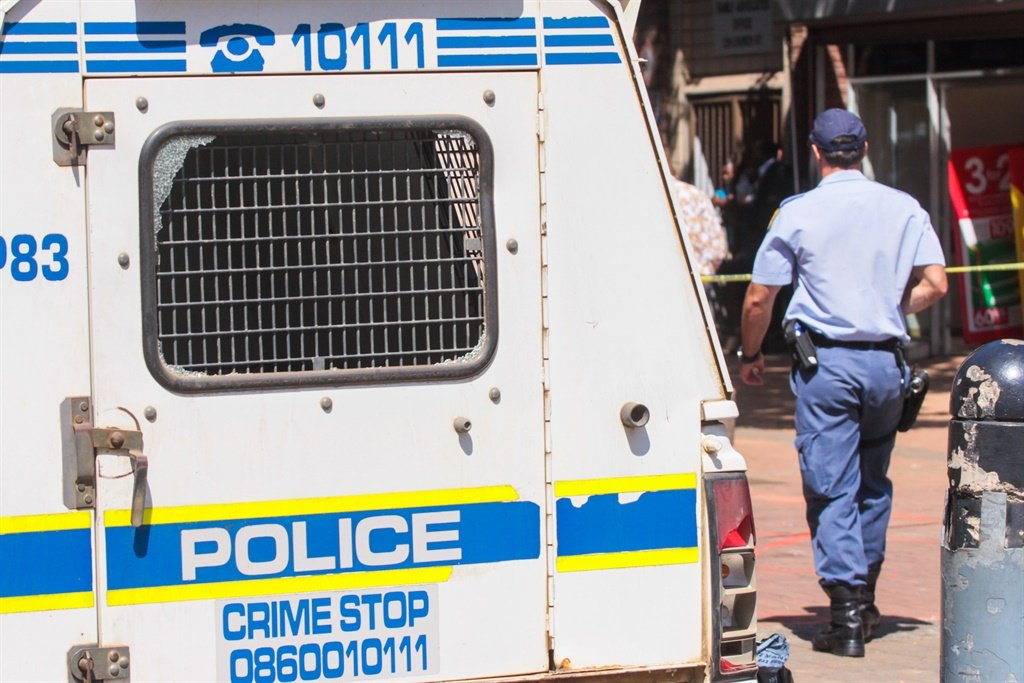 A police officer walks past a SAPS vehicle. File Photo.