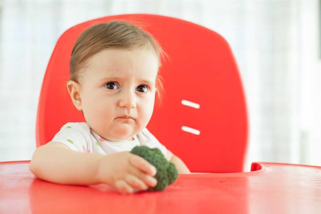 Sad baby girl sitting on high chair holding brocco