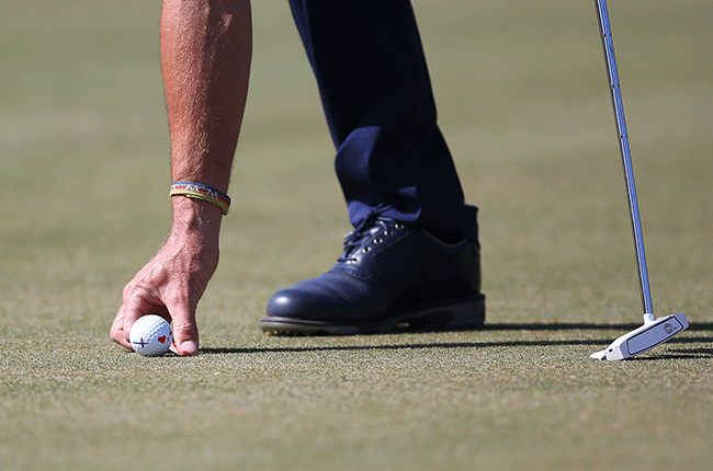 Golfer marking his ball