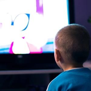 Boy watching television in dark living roomÿÛ