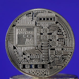 A visual representation of a digital cryptocurrency coin sits on display in front of a Libra logo on June 18, 2019 in Paris, France. (Chesnot/Getty)