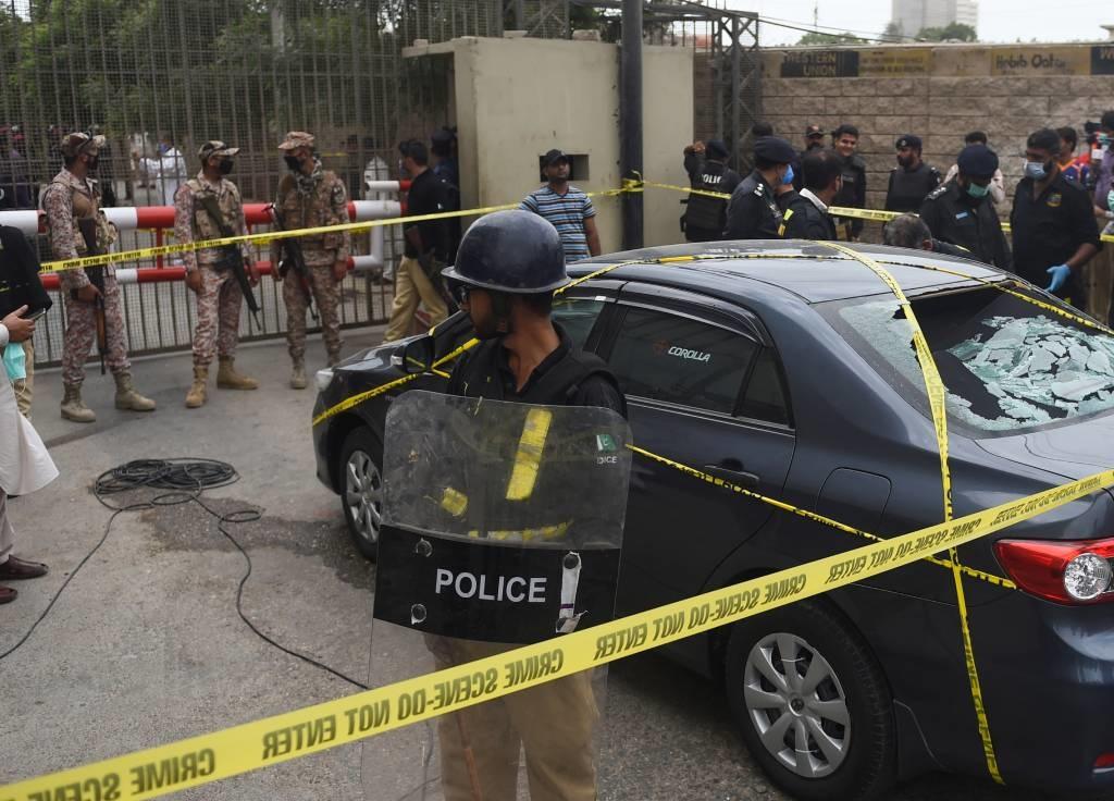 Policemen guard a car used by alleged gunmen outsi