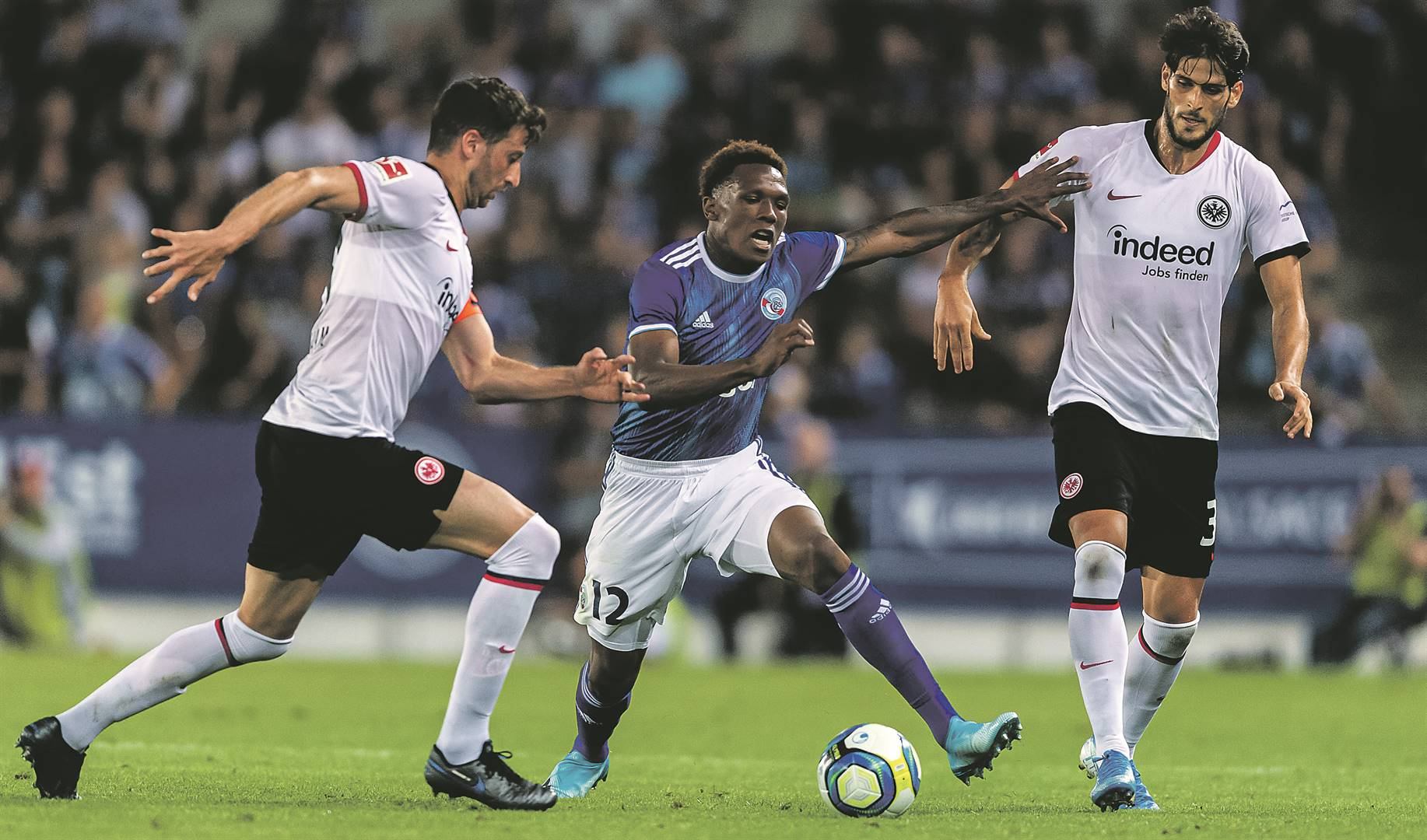 RC Strasbourg striker Lebogang Mothiba, with his distinctive tucked-in shirt, powers his way past Frankfurt defenders David Abraham and Gonçalo Paciência. Mothiba is expected to get playing minutes today. Picture: Alexander Scheuber / Getty Images
