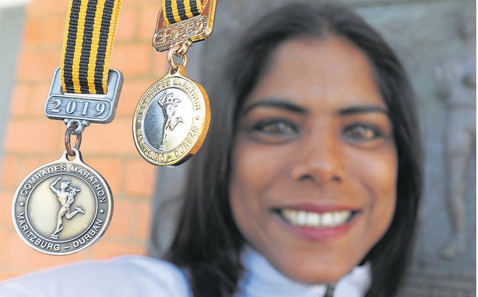 Comrades Marathon Association's media and communications officer, Delaine Cools, holds up two of the new medals, the Robert Mtshali and the Isavel Roche-Kelly medals, that will be awarded to runners in this year's race, which takes place on Sunday. PHOTO: Ian Carbutt
