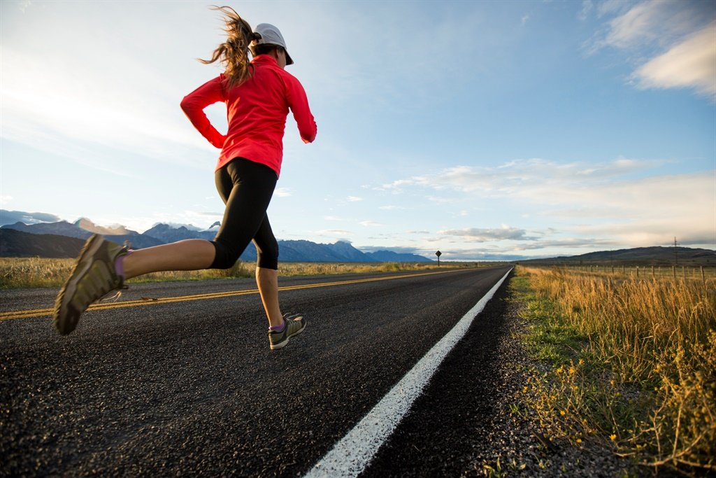 A female running a dirt road in Jackson Hole with