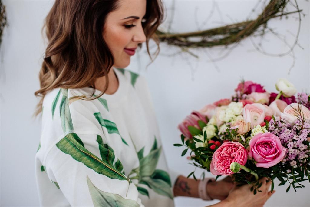 A girl florist makes a bouquet in a light studio o
