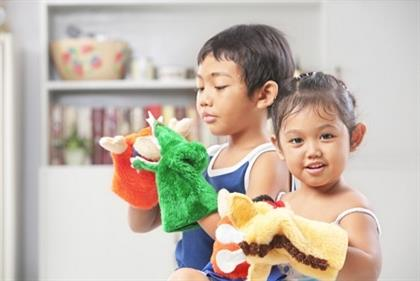 Asian sibling playing hand mad hand-puppet at home