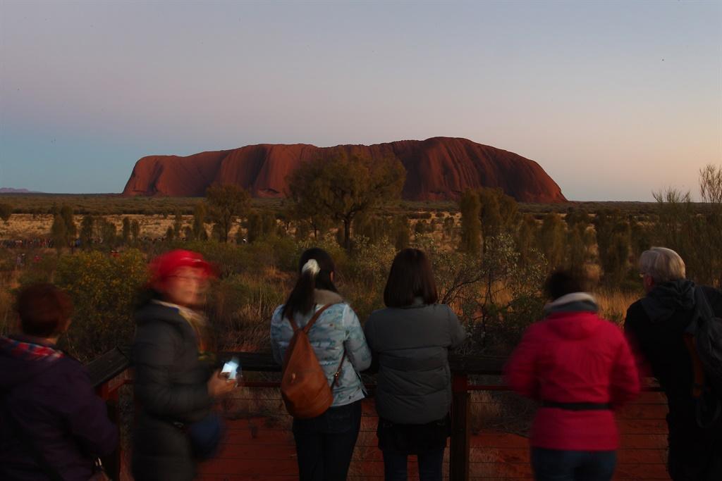 ULURU, AUSTRALIA - AUGUST 14: Park visitors take p
