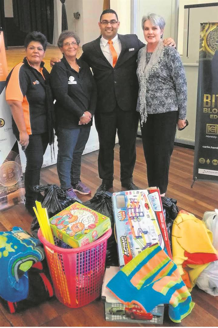 <A Bitcoin education seminar was recently held in the Uitenhage Town Hall. The host, Carlin Hambury of Bitclub Network, took the opportunity to give a donation of clothes and toys to the local NGO, Uitenhage Recycling Mula Shop. Seen here are (from left) Benita George, Glenise Howard (Mula vice chairperson), Carlin Hambury (Bitclub Network) and Quinette Goosen (Mula chair- person).Photo:SUPPLIED