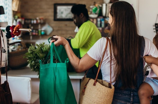 Woman making use of her reusable shopping bag whil