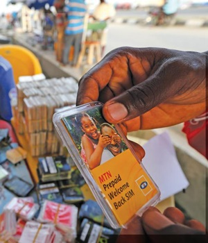 A customer selects an MTN prepaid mobile phone SIM card at a roadside kiosk in Lagos, Nigeria. MTN, Africa's largest wireless operator, remains in negotiations with the Nigerian regulator over a $5.2?billion fine meted out for failing to comply with