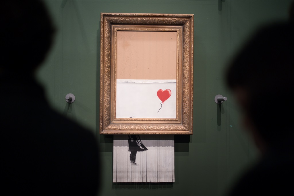 """Stuttgart: Visitors stand in front of the shredded Banksy picture """"Love is in the Bin"""" in the Staatsgalerie. (Photo by Sebastian Gollnow/picture alliance via Getty Images)"""