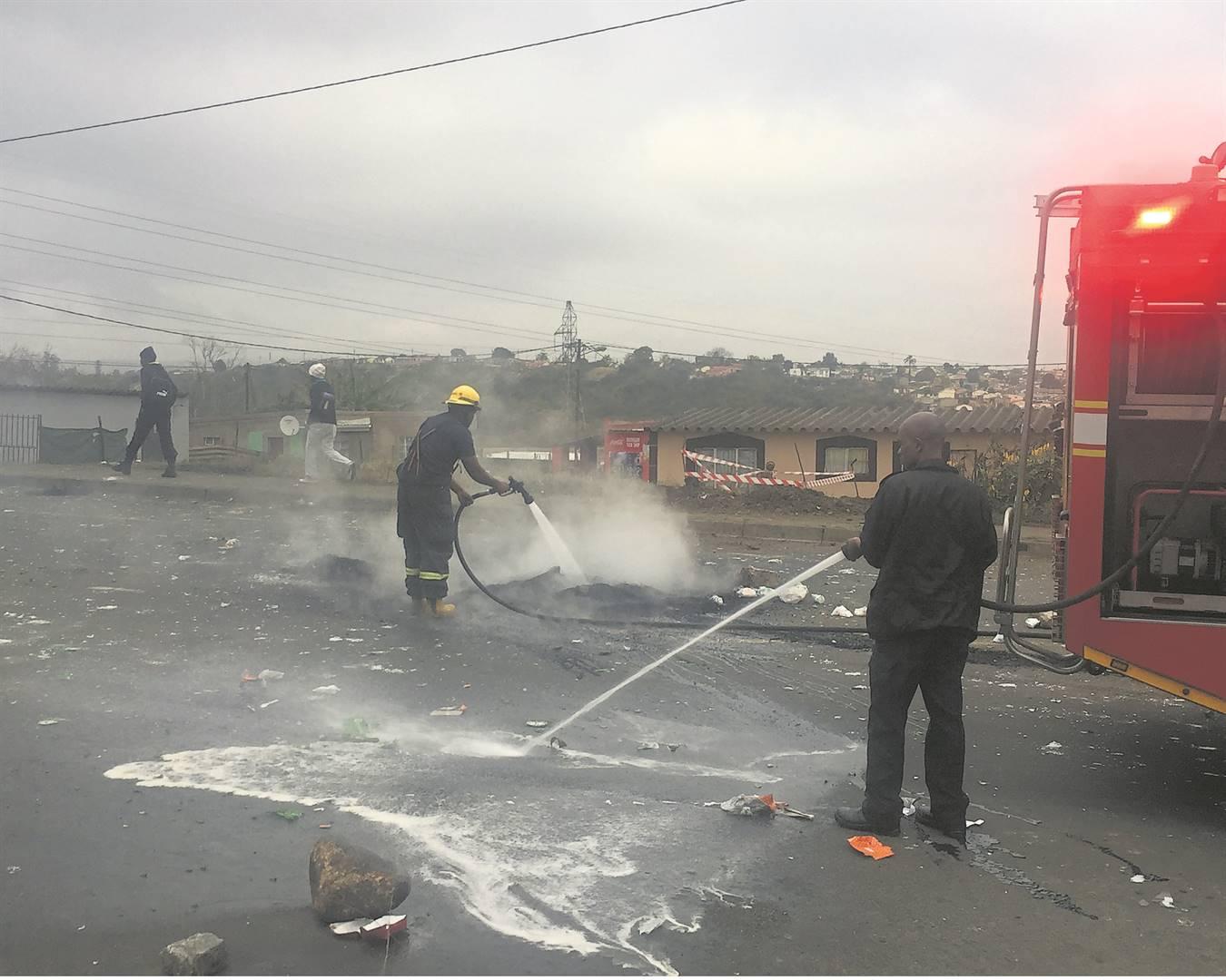 Msunduzi firefighters extinguishing burning debris following a protest on Skhumbuzo Ngwenya Road on Monday morning.
