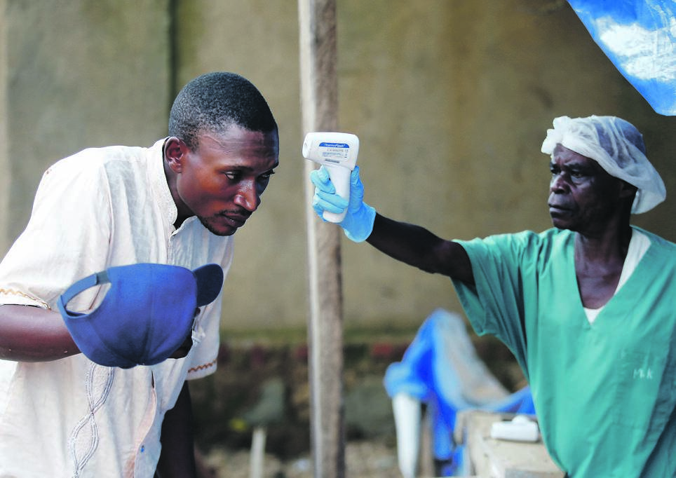 A health worker takes the temperature of a man at the Alliance for International Medical Action Ebola treatment centre in Beni, in the Democratic Republic of Congo. Picture: Baz Ratner / Reuters