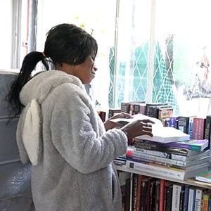 Chantel Fredericks reads a book at the Haven Shelter on Napier Street in Cape Town. (Screengrab)
