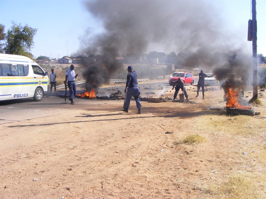 Police officers remove barricades from a road in Siyabuswa in Mpumalanga (Balise Mabona, News24)