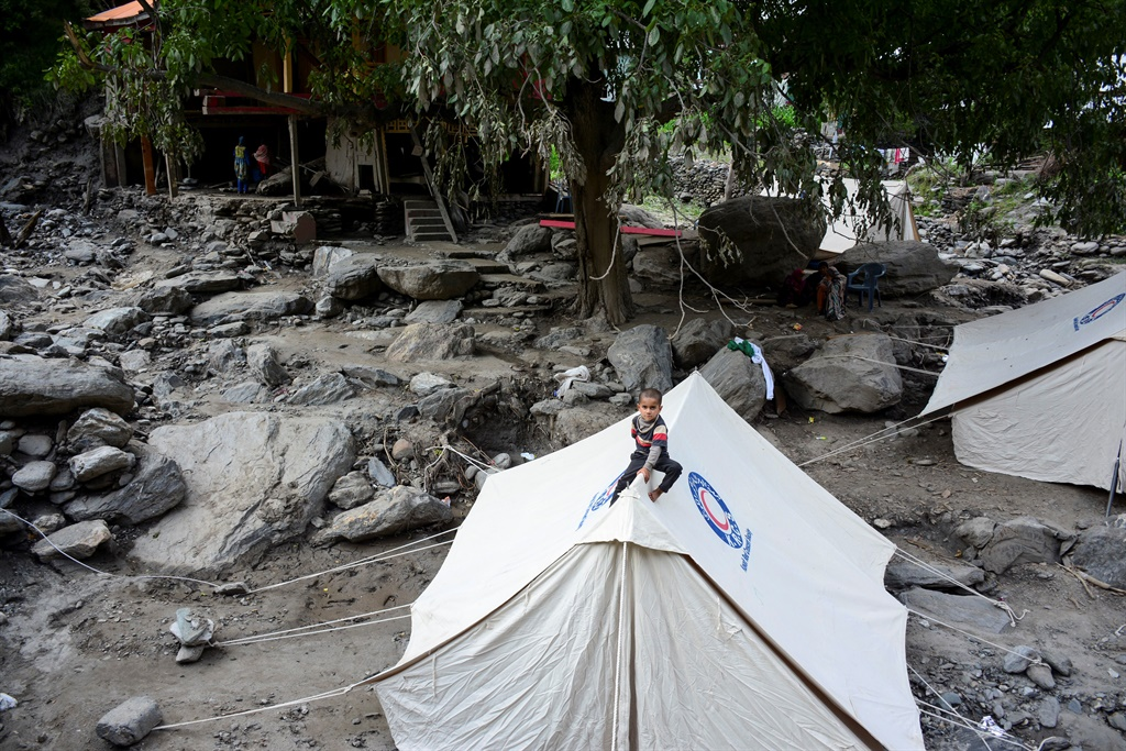 A young Pakistani Kashmiri boy sits over a make-shift tent set up for flood-affected victims in Laswa Valley, near the Line of Control in Pakistan-controlled Kashmir. (Sajjad Qayyum, AFP)
