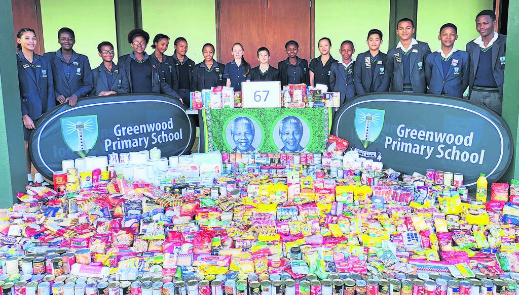 Greenwood Primary School celebrated Mandela Day by having each class collect 67 items to be donated to various charities in Port Elizabeth. Standing around the donations are some of the proud Greenwood learners. Photo:SUPPLIED